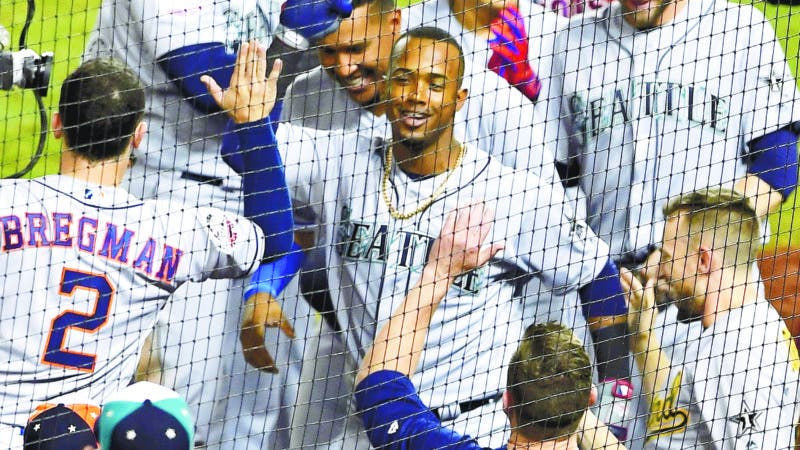 Seattle Mariners Jean Segura (2) center, is greeted at the dugout after his three-run homer in the eighth inning during the Major League Baseball All-star Game, Tuesday, July 17, 2018 in Washington. (AP Photo/Nick Wass)