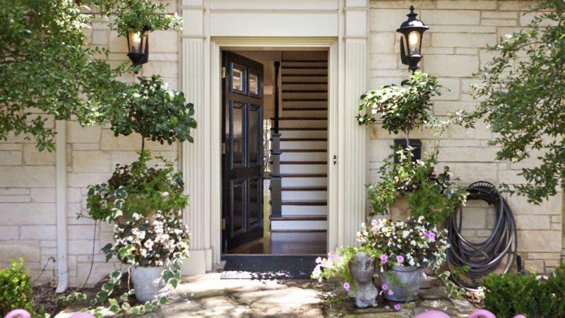 This undated photo provided by Abbe Fenimore shows the delicate leaves and flowers of potted flowering plants which creates a perfect balance with the architectural molding and a dramatic black front door at this entryway designed by Abbe Fenimore of Studio Ten 25 in Dallas, Texas. (Melanie Johnson Photography/Abbe Fenimore via AP)