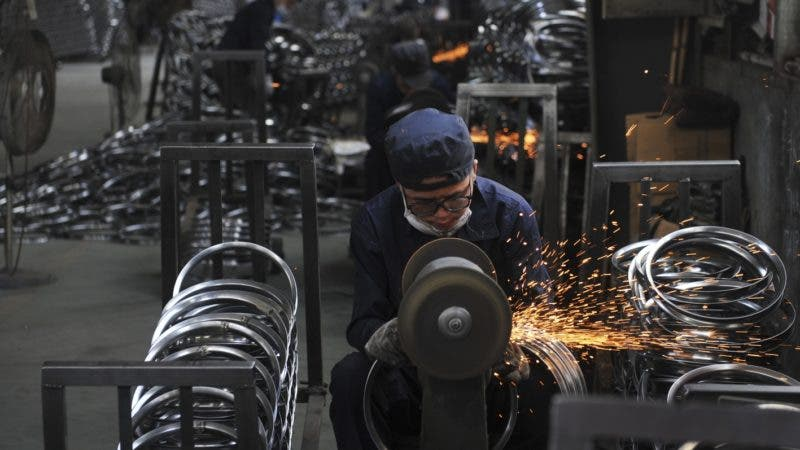 In this June 4, 2018, photo, a worker wields steel wheel rims at a factory in Hangzhou in east China's Zhejiang province. China launched a trade investigation Monday, July 23, 2018 of steel from Europe and South Korea, potentially complicating efforts to recruit them as allies in its tariff dispute with U.S. President Donald Trump. (Chinatopix via AP)