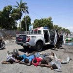 Men lie on the ground as they are arrested by National Police for looting a store selling engine oil, during a protest and general strike in Port-au-Prince, Haiti, Monday, July 9, 2018. A nationwide, general strike and protest has been called for Monday to demand the resignation of Haiti's President Jovenel Moise after his government agreed to reduce subsidies for fuel as part of an assistance package with the IMF. The fuel hike was suspended after widespread, violent protests broke out on Friday and over the weekend. (AP Photo/Dieu Nalio Chery)