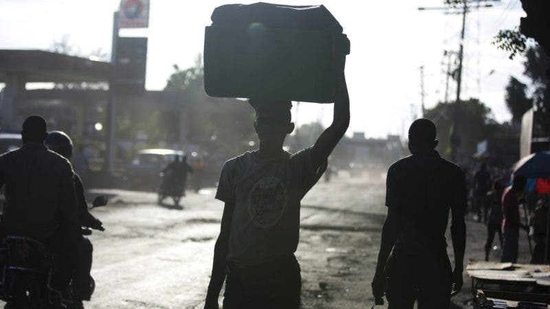 People walk in the street on the second day of a nationwide, general strike in Port-au-Prince, Haiti, early Tuesday, July 10, 2018. While some opposition leaders have called off the strike for Tuesday, most businesses remained closed following days of violent protests against a 50 percent fuel hike, part of a plan endorsed by the IMF to modernize the economy, and calls for the resignation of President Jovenel Moise, whose government suspended the hike. (AP Photo/Dieu Nalio Chery)