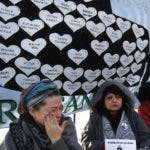 """Lucia Zunda Meoqui, sister of Adrian Zunda Meoqui, left, an Argentine Navy officer of the """"ARA San Juan"""" submarine that sank and disappeared on Nov. 15, 2017, cries as she and others chain themselves to the fence of Government House in Buenos Aires, Argentina, Thursday, June 28, 2018. They are demanding that the Government find the ship. (AP Photo Jorge Saenz)"""