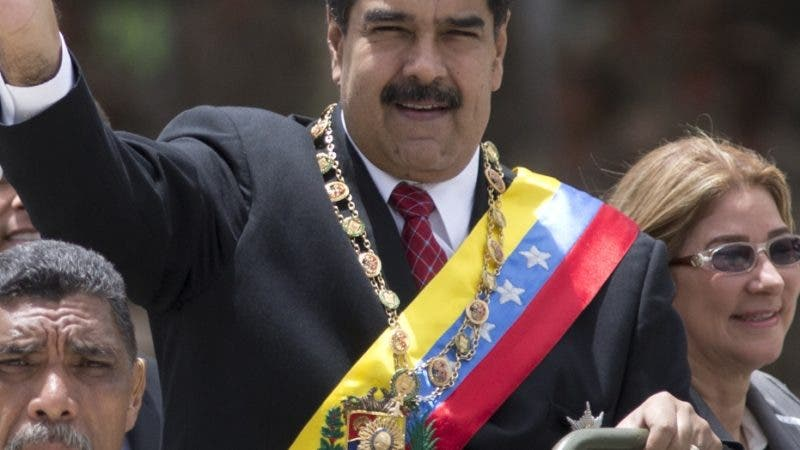 Venezuela's President Nicolas Maduro waves alongside first lady Cilia Flores as they ride in an open vehicle during a military parade marking the Independence Day in Caracas, Venezuela, Thursday, July 5, 2018. Venezuela is marking 207 years of their declaration of independence from Spain. (AP Photos/Ariana Cubillos)