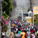 People walk in the street during protests over the fuel price increase in Port-au-Prince, Haiti, on Saturday, July 7, 2018. On Friday, the government announced that it would raise the prices of gasoline, diesel and kerosene from 38 percent to 51 percent beginning Saturday. (AP Photo/Dieu Nalio Chery)