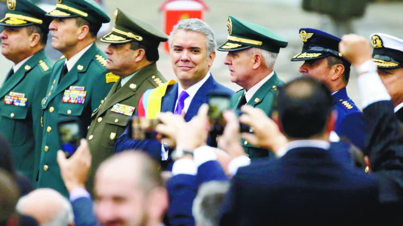 Colombia's newly sworn-in President Ivan Duque reviews the guard of honor with the country's military hierarchy during his inauguration ceremony in Bogota, Colombia, Tuesday, Aug. 7, 2018. (AP Photo/Fernando Vergara)