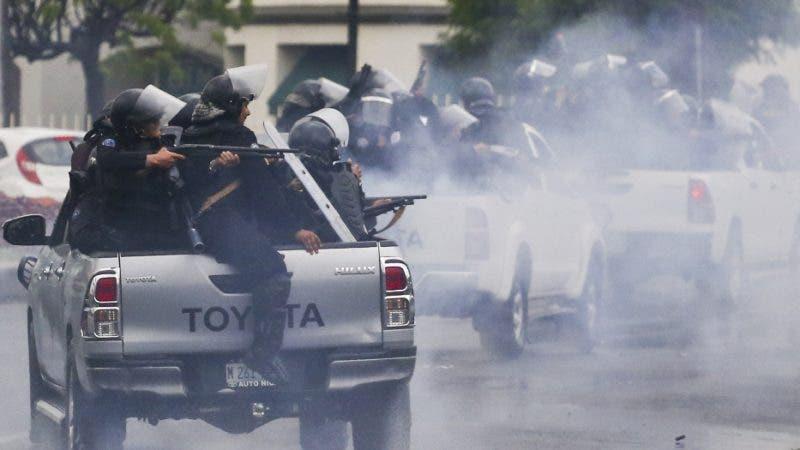 En esta imagen de archivo, tomada el 28 de mayo de 2018, policías con equipos antimotines, montados en la parte trasera de varias camionetas, disparan contra estudiantes universitarios que protestan contra el presidente de Nicaragua, Daniel Ortega, en Managua. (AP Foto/Esteban Félix, archivo)