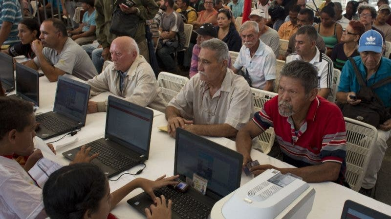Owners of vehicles provide information during a vehicle census announced by Venezuela President Nicolas Maduro as a first step to regulate the sale of gasoline, at Bolivar Square in Caracas, Venezuela, Friday, Aug. 3, 2018. The census started today. (AP Photo/Ariana Cubillos)
