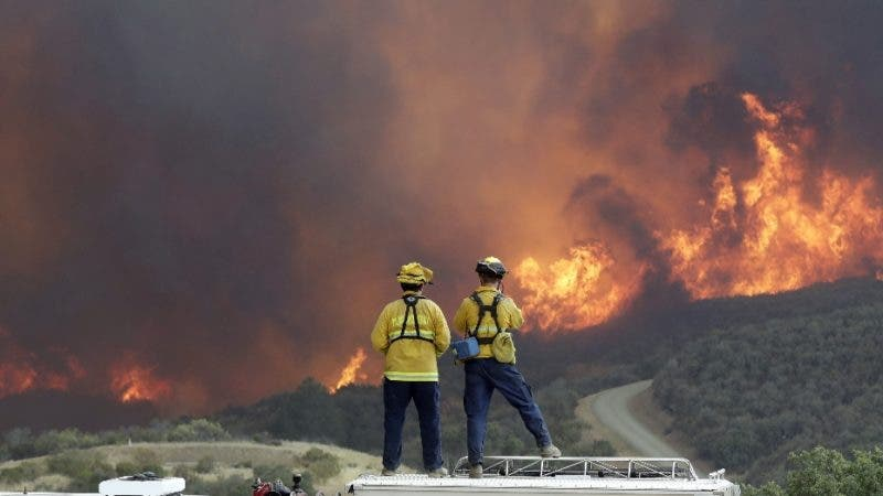 A fire crew from San Luis Obispo County keeps an eye on an advancing wildfire from the perimeter of a residence Tuesday, July 31, 2018, in Lakeport, Calif. Evacuation orders remained in effect Tuesday for the town of Lakeport, the county seat, along with some smaller communities and a section of the Mendocino National Forest. (AP Photo/Marcio Jose Sanchez)
