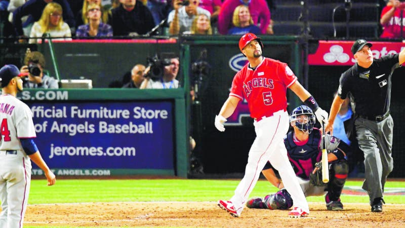 Los Angeles Angels' Albert Pujols watches his solo home run, the 600th homer by Pujols in the majors, as Minnesota Twins starting pitcher Ervin Santana, left, waits along with catcher Chris Gimenez, second from right, and home plate umpire Tim Timmons during the fourth inning of a baseball game, Saturday, June 3, 2017, in Anaheim, Calif. (AP Photo/Mark J. Terrill)