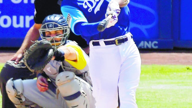 Los Angeles Dodgers' Manny Machado, right, hits a two-run home run as San Diego Padres catcher Austin Hedges watches during the fifth inning of a baseball game Sunday, Aug. 26, 2018, in Los Angeles. (AP Photo/Mark J. Terrill)