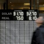 A man walks by an exchange office in Buenos Aires, Argentina, Wednesday, Aug. 29, 2018. The Argentine currency fell again to an all-time low of 34,5 pesos for every U.S. dollar. President Mauricio Macri has asked the International Monetary fund for an early release of funds from a $50 billion deal with the IMF to ease concerns that Argentina will not be able to meet its debt obligations for 2019. (AP Photo/Natacha Pisarenko)