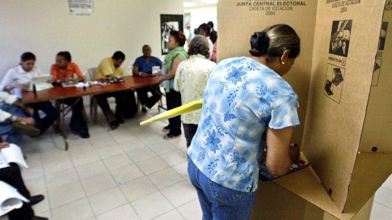 Una mujer sufraga en las elecciones presidenciales del 16 de mayo de 2004 en la ciudad de Santo Domingo. La muerte de dos militantes del oficialismo y uno de la oposicion liberal ensombrecieron en la mañana del domingo los comicios, que registran una masiva y entusiasta asistencia entre denuncias aisladas de dificultades para votar. Miles de dominicanos formaron largas filas en los 12.102 colegios electorales establecidos en todo el pa's para que voten 5,02 millones personas. Otros 52.440 electores lo harin por primera vez en el exterior.  AFP PHOTO/Juan BARRETO