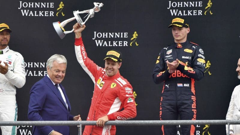 Ferrari driver Sebastian Vettel of Germany, center, jubilates with his trophy on the podium after winning the Belgian Formula One Grand Prix in Spa-Francorchamps, Belgium, Sunday, Aug. 26, 2018. Mercedes driver Lewis Hamilton of Britain, left, placed second and Red Bull driver Max Verstappen of the Netherlands, second right, placed third. (AP Photo/Geert Vanden Wijngaert)