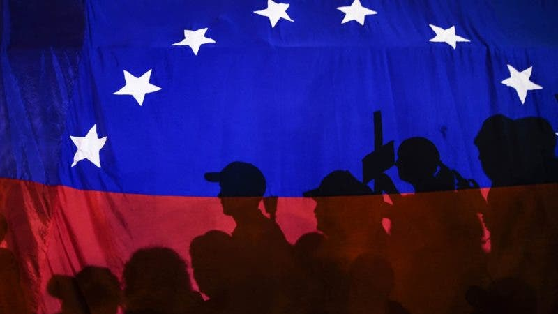Opposition activists, seen here behind a Venezuelan flag, protest against the deaths of 43 people in clashes with the police during weeks of demonstrations against the government of Venezuelan President Nicolas Maduro, in Caracas on May 17, 2017.  The United States warned on Wednesday at the United Nations that Venezuela's crisis was worsening and could escalate into a major conflict similar to Syria or South Sudan. / AFP PHOTO / JUAN BARRETO