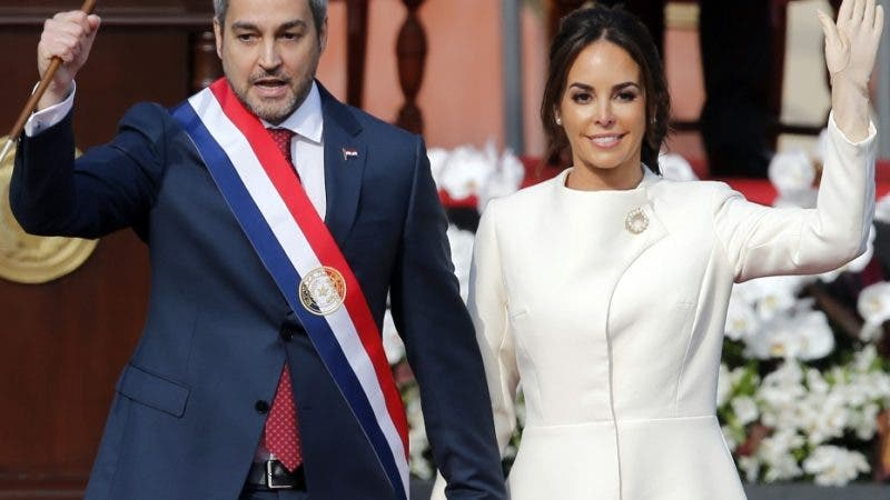 """Paraguay's new President Mario Abdo Benitez, flanked by his wife Silvana Lopez, acknowledges the crowd after taking the oath of office at """"Lopez Palace"""" in Asuncion, Paraguay, Wednesday, Aug. 15, 2018. Abdo Benitez is Paraguay's 50th President. (AP Photo/Jorge Saenz)"""