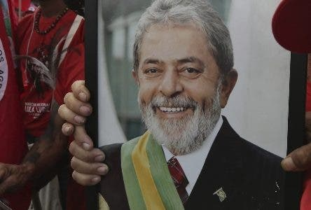 Supporters holding a photo of Brazil's jailed former president Luiz Inacio Lula da Silva takes part in the Free Lula March, in Brasilia, Brazil, Wednesday, Aug.15 2018. Thousands of supporters of the jailed leader and a current presidential candidate, are in Brasilia to monitor the registration of Lula's presidential candidacy, which will be held today by the Workers' Party in the Superior Electoral Court. (AP Photo/Eraldo Peres)