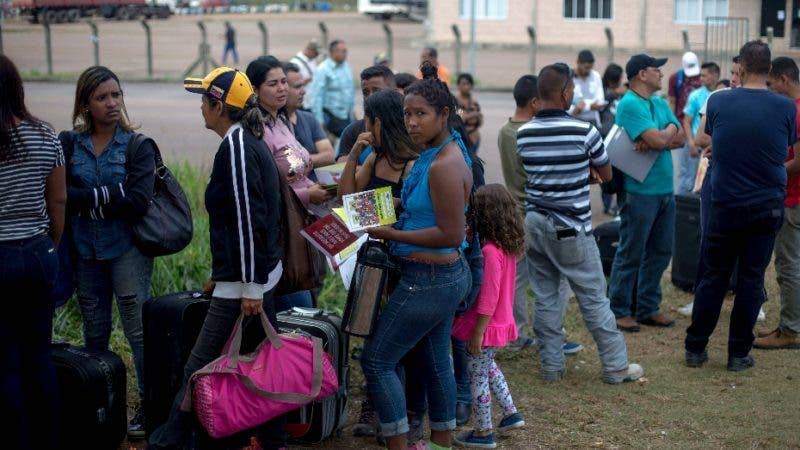 Venezuelans wait in a queue in front of the Brazil Federal Police Office in the Venezuela-Brazil border, at Pacaraima, Roraima, Brazil, on February 28, 2018.   According to local authorities, around one thousand refugees are crossing the Brazilian border each day from Venezuela. With the constant influx of Venezuelan immigrants, most are living in shelters and the streets of Boa Vista and Pacaraima cities, looking for work, medical care and food. Most are legalizing their status to stay and live in Brazil.  - TO GO WITH AFP STORY by Paula RAMÓN  / AFP / Mauro Pimentel / TO GO WITH AFP STORY by Paula RAMÓN