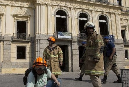 A National Museum worker organizes pieces rescued from the museum after an overnight fire in Rio de Janeiro, Brazil, Monday, Sept. 3, 2018. A huge fire engulfed Brazil's 200-year-old National Museum in Rio de Janeiro, lighting up the night sky with towering flames as firefighters and museum workers raced to save historical relics from the blaze. (AP Photo/Silvia Izquierdo)