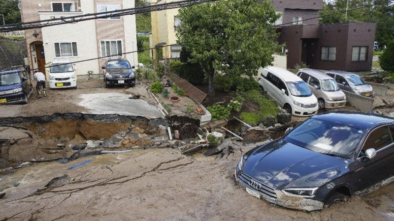 Cars are stuck in mud covered road after an earthquake in Sapporo, Hokkaido, northern Japan, Thursday, Sept. 6, 2018. A powerful earthquake shook Japan's northernmost main island of Hokkaido early Thursday, causing landslides that crushed homes, knocking out power across the island. (Hiroki Yamauchi/Kyodo News via AP)