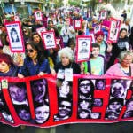 The relatives of members of the Association of Executed Politicians carry photos of their dead family members during a march marking the 45th anniversary of the 1973 military coup that toppled Chile's late President Salvador Allende, days before the anniversary in Santiago, Chile, Sunday, Sept. 9, 2018. The coup began the 1973-1990 military dictatorship of Gen. Augusto Pinochet on Sept. 11. (AP Photo/Esteban Felix)