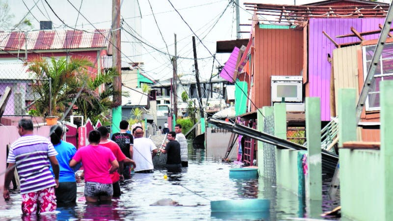"""People walk in a flooded street next to damaged houses in Catano town, in Juana Matos, Puerto Rico, on September 21, 2017. Puerto Rico braced for potentially calamitous flash flooding after being pummeled by Hurricane Maria which devastated the island and knocked out the entire electricity grid. The hurricane, which Puerto Rico Governor Ricardo Rossello called """"the most devastating storm in a century,"""" had battered the island of 3.4 million people after roaring ashore early Wednesday with deadly winds and heavy rain. / AFP / HECTOR RETAMAL"""