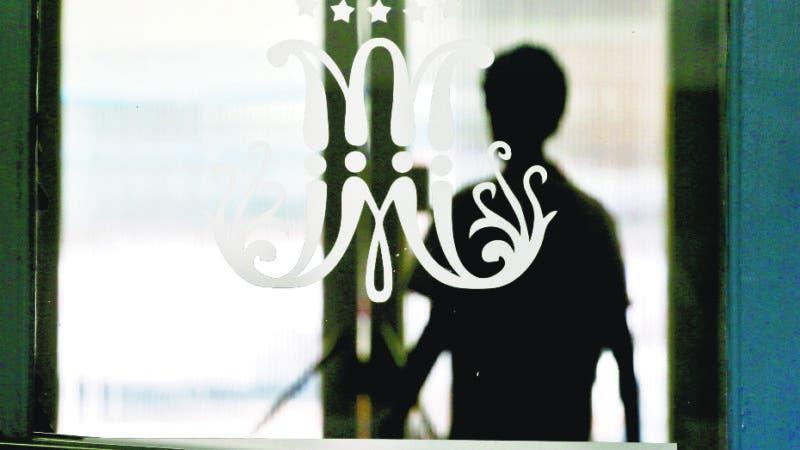 En esta imagen, tomada el 2 de abril de 2018, se muestra un logo formado por una letra M de gran tamaño en cursiva con 12 estrellas, un símbolo que se identifica con los Maristas, adornando una puerta de cristal, con la silueta de de un estudiante de fondo, en el instituto Alonso de Ercilla en Santiago, Chile. Los maristas revelaron que al menos 14 menores sufrieron abusos entre la década de 1970 y 2008 por un hermano que trabajó en dos escuelas de la orden. (AP Foto/Esteban Félix)