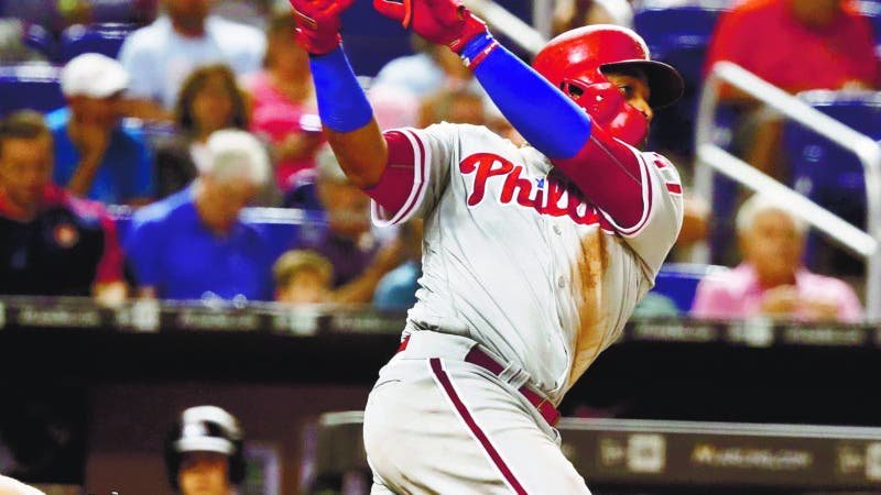 Philadelphia Phillies' Carlos Santana, right, hits a single during the fourth inning of a baseball game against the Miami Marlins, Monday, Sept. 3, 2018, in Miami. (AP Photo/Brynn Anderson)