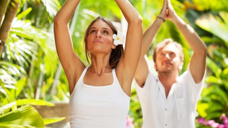 Young couple doing yoga outdoor in a tropical resort.
