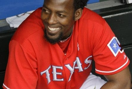 Texas Rangers' Vladimir Guerrero smiles as he holds a bundle of roses in the dugout waiting to present them to his mother before the Rangers' baseball game against the Kansas City Royals, Sunday, May 9, 2010, in Arlington, Texas. (AP Photo/Tony Gutierrez)