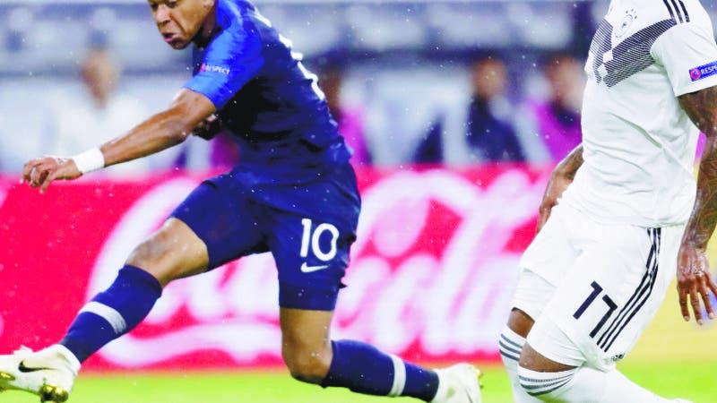 Kylian Mbappé, de la selección de Francia, dispara junto a Jerome Boateng, de Alemania, en un partido de la Liga de Naciones de la UEFA, el jueves 6 de septiembre de 2018, en Múnich (AP Foto/Michael Probst)