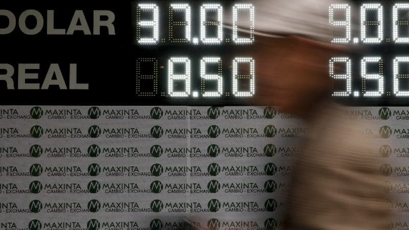 A man walks past a sign announcing the price of U.S. dollar and Brazilian real, in exchange for Argentine pesos, at an exchange house in Buenos Aires, Argentina, Monday, Sept. 3, 2018. Argentina's President Mauricio Macri has announced new taxes on exports and the elimination of several ministries on Monday in a bid to halt economic turmoil that has sent the peso to record lows. (AP Photo/Natacha Pisarenko)