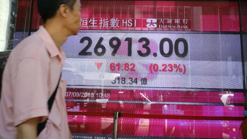 A man walks past an electronic board showing Hong Kong share index outside a local bank in Hong Kong, Friday, Sept. 7, 2018. Asian stocks were mostly lower on Thursday as the U.S. and China moved closer to imposing tariffs on billions of dollars of each other's goods, sounding a call of caution in the markets. (AP Photo/Vincent Yu)