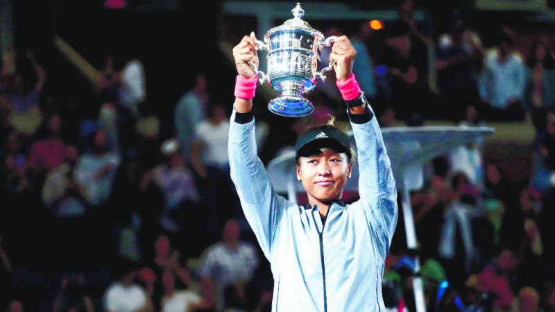 Naomi Osaka, of Japan, holds up the championship trophy after defeating Serena Williams in the women's final of the U.S. Open tennis tournament, Saturday, Sept. 8, 2018, in New York. (AP Photo/Andres Kudacki)