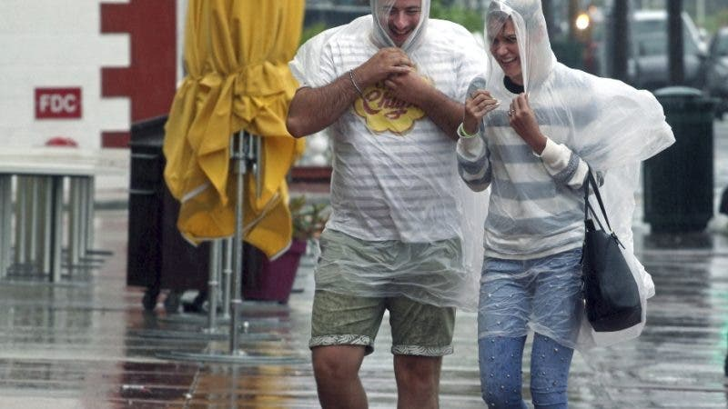 South Beach tourists brave the rain as a tropical storm warning was issued for the Miami Beach, Fla., Monday, Sept. 3, 2018. Tropical Storm Gordon lashed South Florida with heavy rains and high winds on Monday, forcing holiday beachgoers to drier ground. (Carl Juste/Miami Herald via AP)