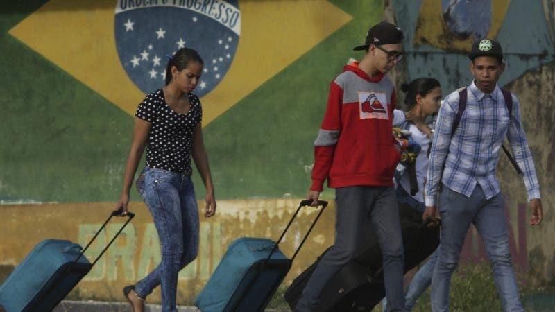 ARCHIVO - En esta fotografía de archivo del 9 de marzo de 2018, unos venezolanos avanzan con su equipaje tras cruzar la frontera entre Brasil y Venezuela en la ciudad de Pacaraima, en el estado brasileño de Roraima. (AP Foto/Eraldo Peres, archivo)