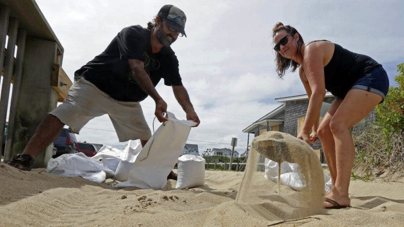 Steve and Jamie Galloway bag sand Wednesday, Sept. 12, 2018, in Kill Devil Hills, N.C., as Hurricane Florence approaches the east coast. (AP Photo/Gerry Broome)