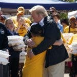 President Donald Trump hugs a young man while handing out prepackaged meals at Temple Baptist Church in an area impacted by Hurricane Florence, Wednesday, Sept. 19, 2018, in New Bern, N.C.