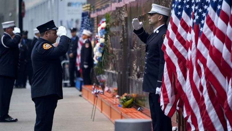 New York City firefighters salute in front of a memorial on the side of a firehouse adjacent to One World Trade Center and the 9/11 Memorial site during ceremonies on the anniversary of 9/11 terrorist attacks in New York on Tuesday, Sept. 11, 2018. (AP Photo/Craig Ruttle)
