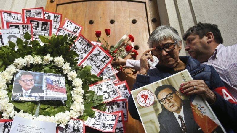 Elena Araneda, who worked for the administration of late President Salvador Allende, cries after placing a flower outside the eastern entrance of La Moneda presidential palace on the anniversary of the coup and Allende's death in Santiago, Chile, Tuesday, Sept. 11, 2018. It was through this entrance that Allende's body was carried by soldiers and firefighters from the destroyed presidential palace 45 year ago during the 1973 military coup that ousted the democratically elected leader and began the 17-year dictatorship of Gen. Augusto Pinochet. (AP Photo/Esteban Felix)