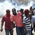 Demonstrators run for cover as Haitian police fire tear gas to disperse an anti-government protest in the centre of the Haitian capital Port-au-Prince, on September 12, 2017.  Demonstrators took to the streets to protest against the government and the new budget for 2018, throwing stones at the police, setting tires on fire and blocking some streets. / AFP / HECTOR RETAMAL