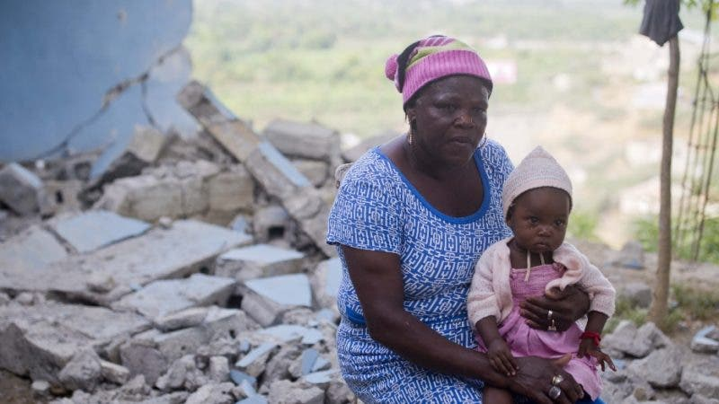 Lodanise Joseph sits with her 9-month-old granddaughter outside their home damaged in the quake that hit over the weekend in Port-de-Paix, Haiti, Monday, Oct. 8, 2018. The death toll from a 5.9 earthquake that hit Haiti over the weekend rose to at least 15 people with hundreds injured, according to updated figures released Monday by authorities, as rescue crews worked to help victims spooked by strong aftershocks. (AP Photo/Dieu Nalio Chery)