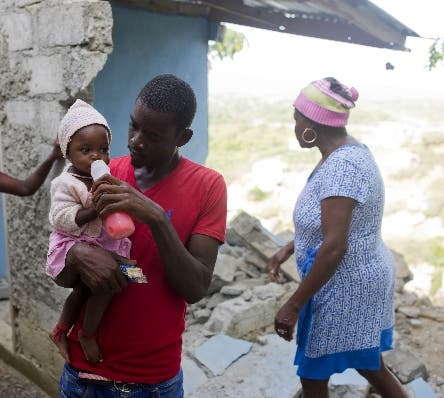 """Marc-Sena Docteur feeds his 9-month-old daughter Size, outside their home damaged in the quake that hit over the weekend in Port-de-Paix, Haiti, Monday, Oct. 8, 2018. Docteur's girlfriend died in the earthquake. """"Now I'm left with a 9-month-old baby with no aid at all,"""" he said. """"I'm still crying. I don't know what I'm going to do without her."""""""