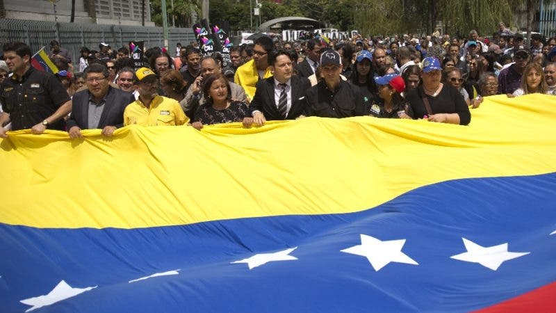 Opposition leaders and friends holds a giant Venezuela flag as they walk behind the hearse containing the remains of opposition activist Fernando Alban, during his funeral in Caracas, Venezuela, Wednesday, Oct. 10, 2018. Hundreds gathered to pay their respects to Alban. International condemnation of Venezuela's leadership poured in Tuesday following the suspicious death of the opposition activist authorities say evaded justice by throwing himself from the 10th floor of a police building. (AP Photo/Ariana Cubillos)