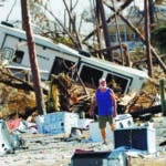 Ronnie Poole walks through debris as he checks on a friend's home in the aftermath of Hurricane Michael in Mexico Beach, Fla., Wednesday, Oct. 17, 2018. (AP Photo/Gerald Herbert)