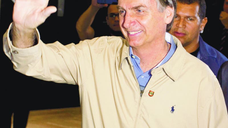 Presidential candidate Jair Bolsonaro, with the Social Liberal Party, waves to the press after visiting Federal Police headquarters in Rio de Janeiro, Brazil, Wednesday, Oct. 17, 2018. Bolsonaro won the first round of the presidential election Oct. 7 with 46 percent of the vote, but since he failed to top 50 percent, he is in a second-round ballot on Oct. 28. (AP Photo/Silvia Izquierdo)