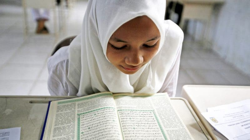 INDONESIA CORÁN:BA01 BANDA ACEH (INDONESIA) 12/06/2015.- Una joven estudiante lee el Corán durante su examen de lectura del mismo en Banda Aceh (Indonesia) hoy, viernes 12 de junio de 2015. La prueba de lectura del Corán es uno de los requisitos para continuar su educación secundaria. Aceh es la única provincia indonesia en la que se aplica la ley Sharia. EFE/Hotli Simanjuntak