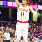 Atlanta Hawks' Trae Young (11) shoots over Cleveland Cavaliers' Collin Sexton (2) in the second half of an NBA basketball game, Sunday, Oct. 21, 2018, in Cleveland. The Hawks won 133-111. (AP Photo/Tony Dejak)