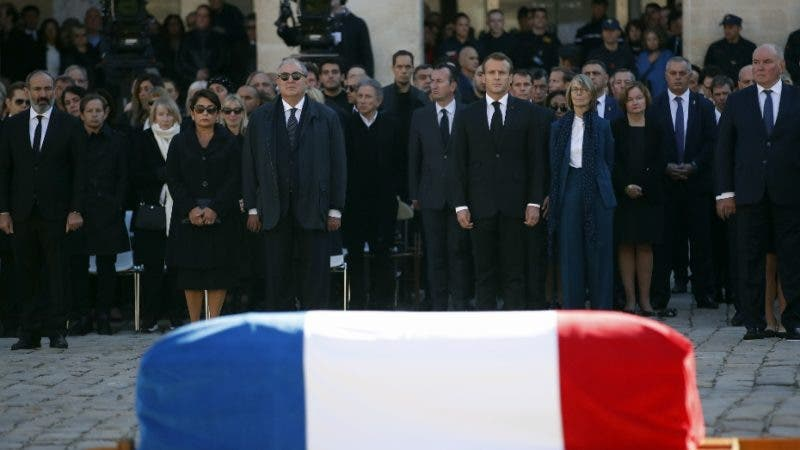 French President Emmanuel Macron, center, right, and officials stand behind the coffin during a ceremony to pay tribute to late singer Charles Aznavour, Friday, Oct.5, 2018 in Paris. France paid tribute to Charles Aznavour on Friday in a solemn and subdued ceremony that contrasted sharply with the singer's joyful character. (AP Photo/Christophe Ena, Pool)