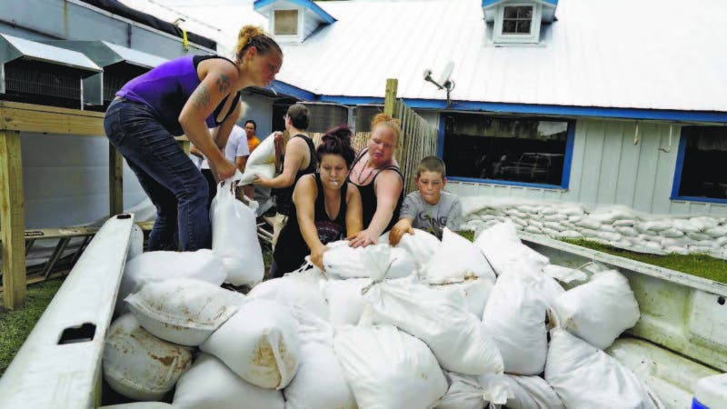 Krystal Day, of Homosassa, Fla., left, leads a sandbag assembly line at the Old Port Cove restaurant Tuesday, Oct. 9, 2018, in Ozello, Fla. Employees were hoping to protect the restaurant from floodwaters as Hurricane Michael continues to churn in the Gulf of Mexico heading for the Florida panhandle. (AP Photo/Chris O'Meara)
