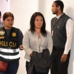 In this photo provide by Peru's Justice Department, Keiko Fujimori enters the chief prosecutor's office, with a jacket covering her handcuffs, in Lima, Peru, Wednesday, Oct. 10, 2018. Fujimori was detained on Wednesday as part of a money-laundering investigation, the latest political leader in the Andean nation to face scrutiny over alleged corruption. (Peru's Justice Department via AP)